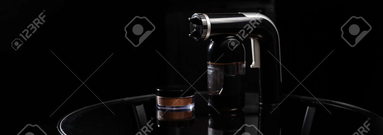 A close-up of the instant tanning equipment. Gun spraying paint for leather and matting body powder on a black background - 170497164