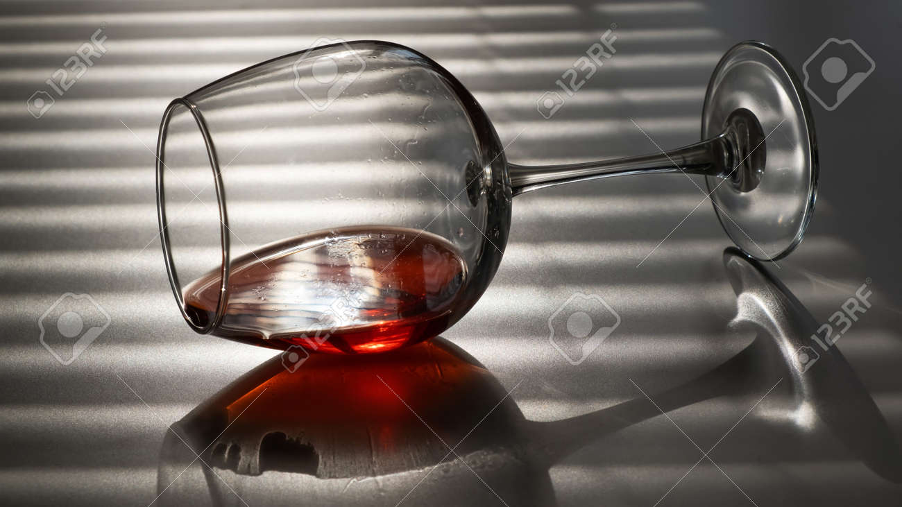 A glass of red wine lies on its side on a white table with a shade from the blinds - 170510260