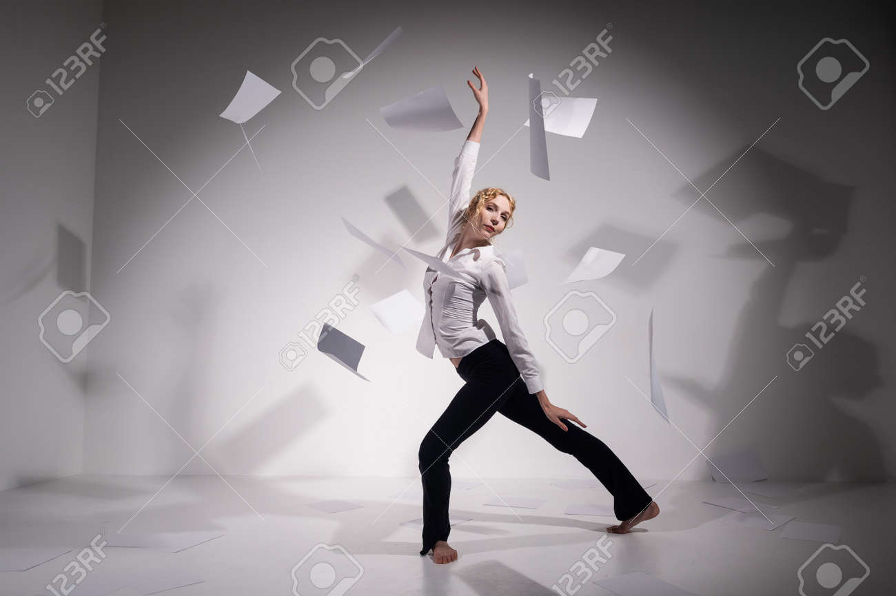 A graceful ballerina in a business suit throws documents in the studio. Business woman dance barefoot on a white background - 170510359