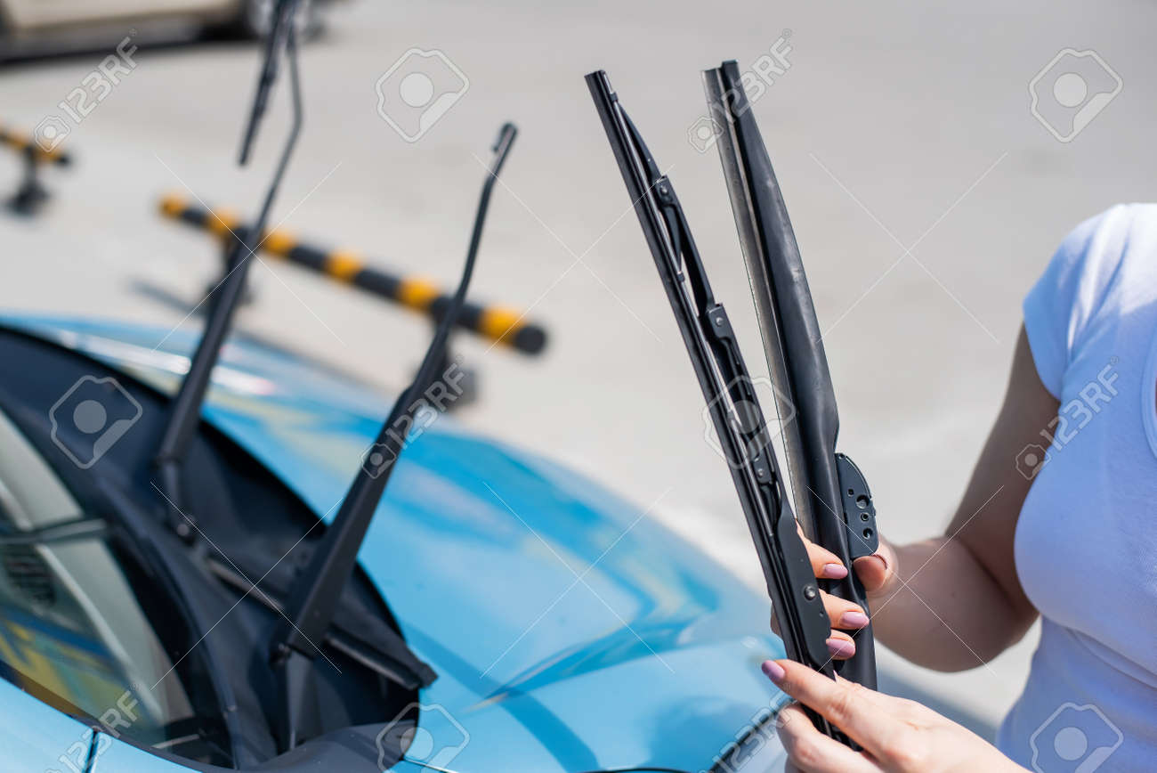 Faceless woman changing car windshield wipers. - 170559439