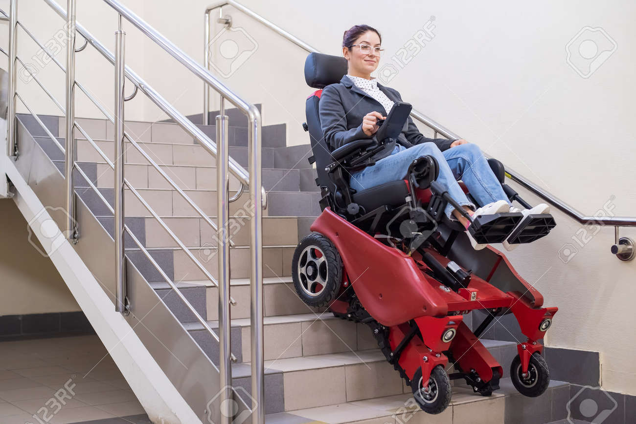 Caucasian woman in electric caterpillar wheelchair climbs up stairs. - 171721748