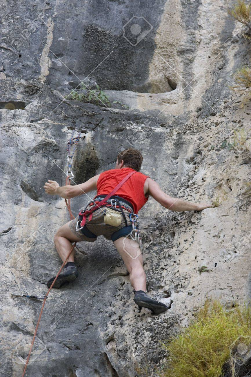 Man in red climbing on limestone rock in thailand Stock Photo - 3084480