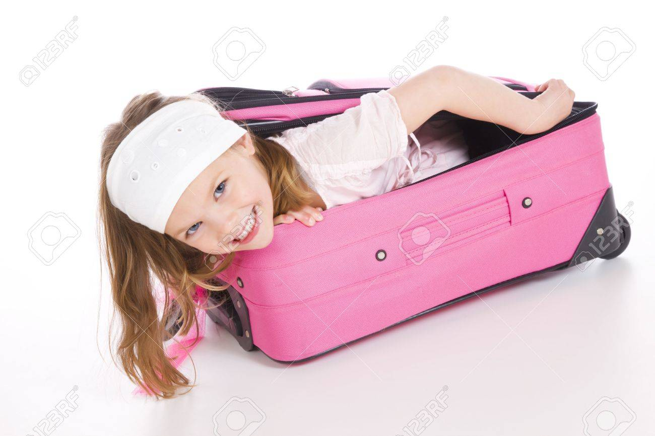 young girl getting ready for travelling by fitting into suitcase. Stock Photo - 6679379