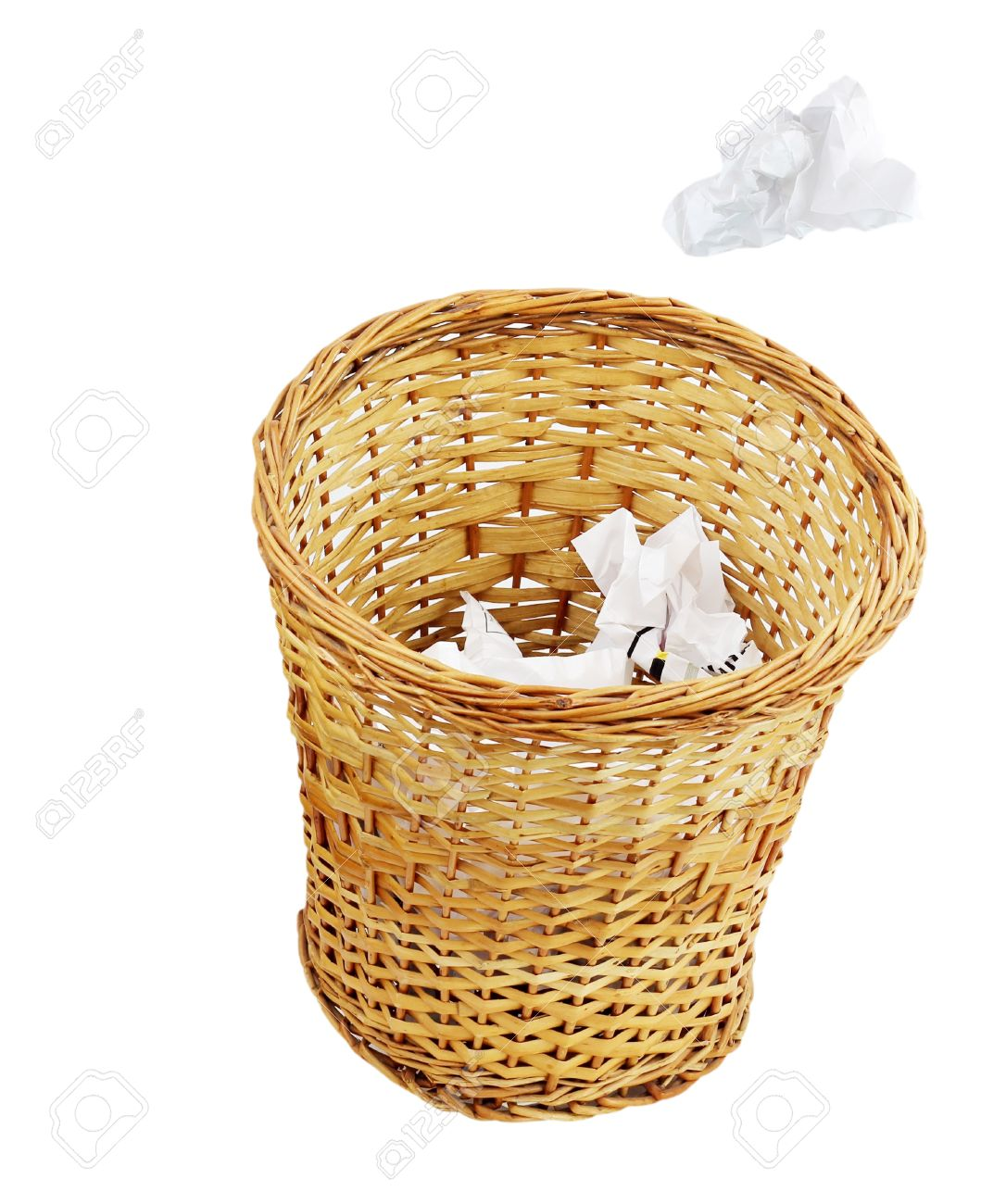 A Crumpled Paper Being Thrown Into A Wicker Trash Can Isolated