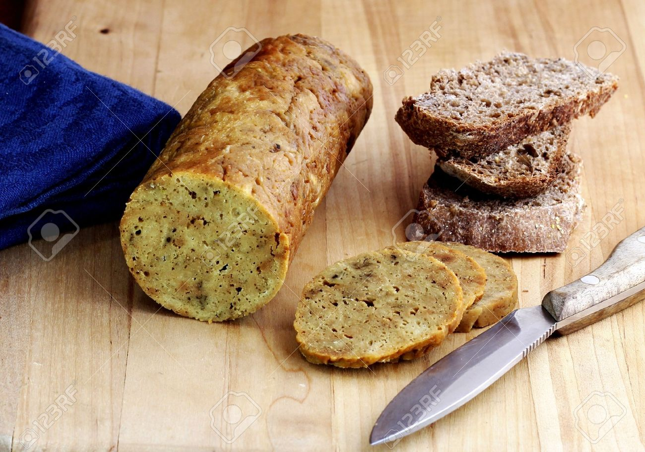 A healthy vegan snack: A roll of vegan seitan on a cutting board with slices of rye bread Stock Photo - 9421080