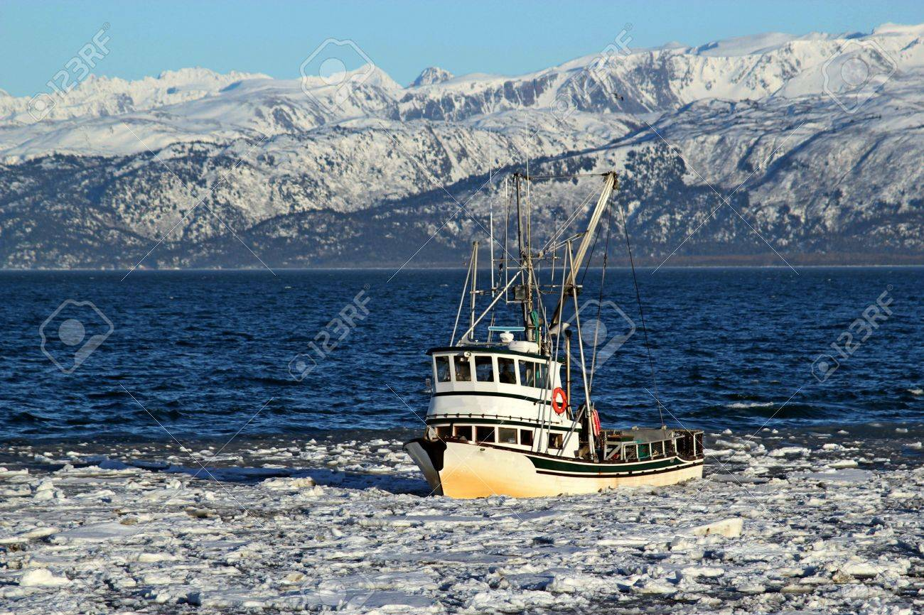 Classic fishing boat traveling through ice in the Kachemak bay near Homer, Alaska with the Kenai mountains in the background on a sunny winter day. Stock Photo - 12538976