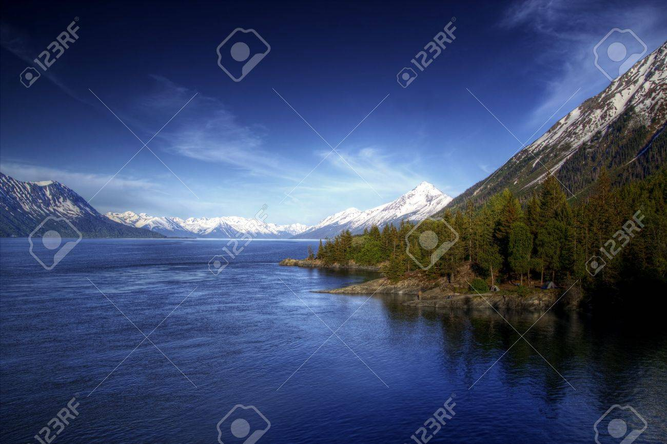 View of the water of the Turnagain Arm near Hope Alaska in soft evening light with bright blue skies. Stock Photo - 14064597