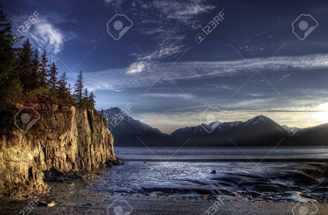 Beach on the Turnagain Arm near Hope Alaska at low tide with interesting patterns in the sand and cliffs illuminated by the evening light. Stock Photo - 14064600