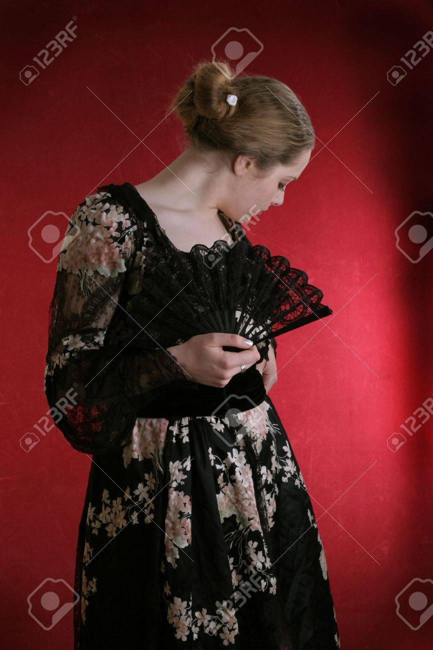 pretty young lady in old time ball dress with black fanStanding