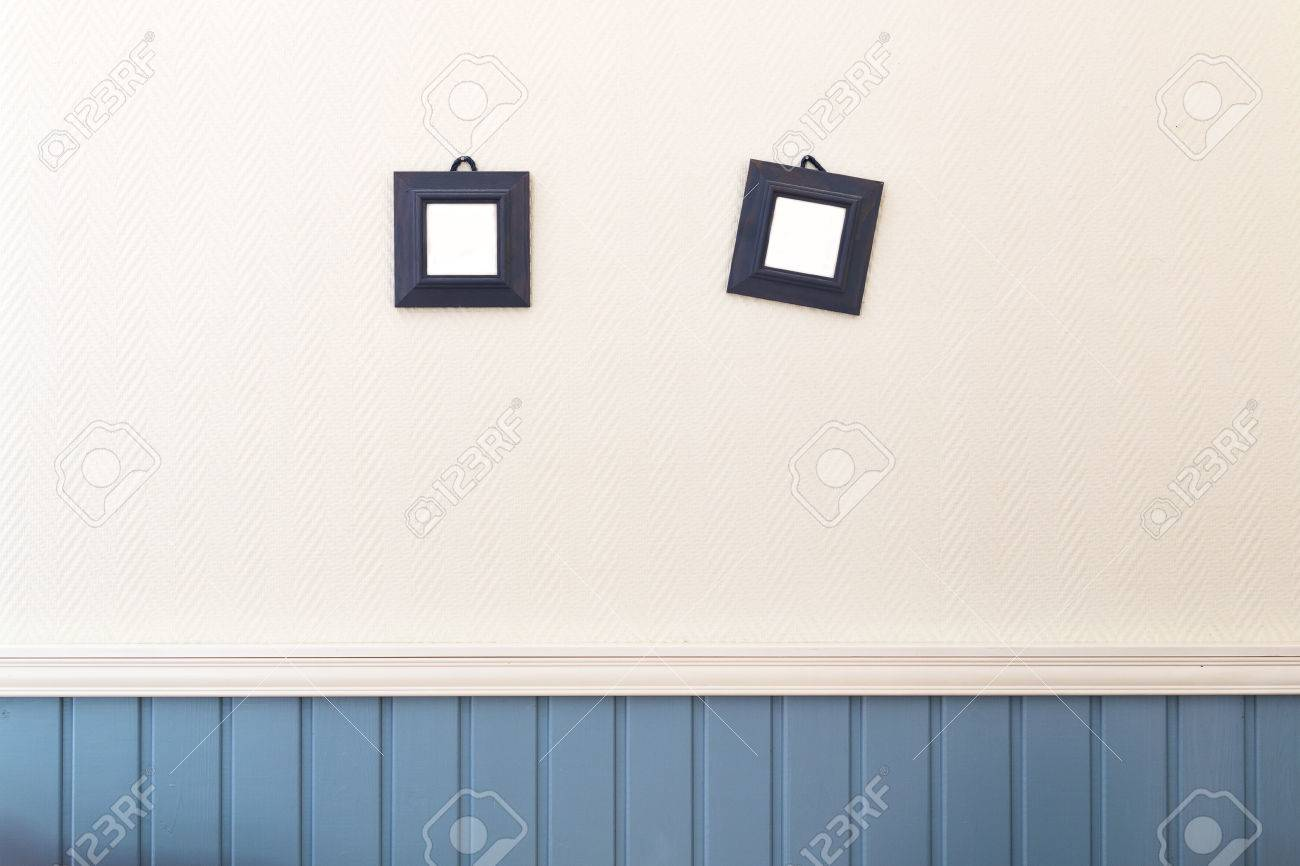 Two Small Square Frames Hanging On The White And Blue Wall Stock ...