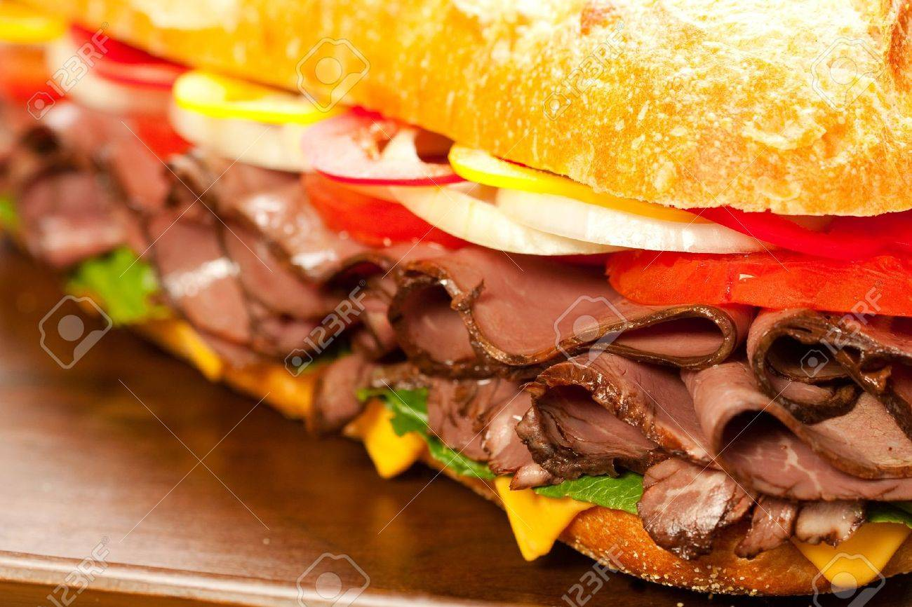 Large roast beef sandwich with cheese, lettuce, tomatoes, onion, red and yellow peppers. Stock Photo - 7213133