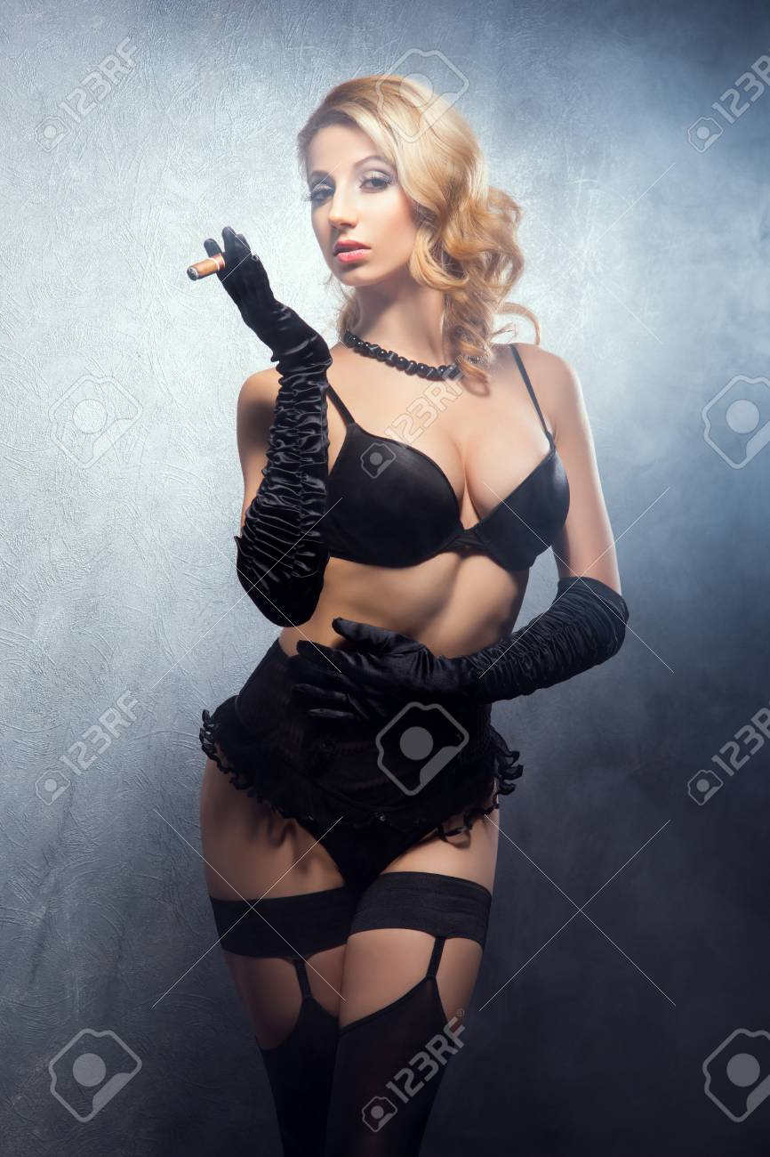 7a3ddab5d6370 Stock Photo - Young and beautiful cabaret dancer in sexy vintage lingerie  smoking cigar over retro background