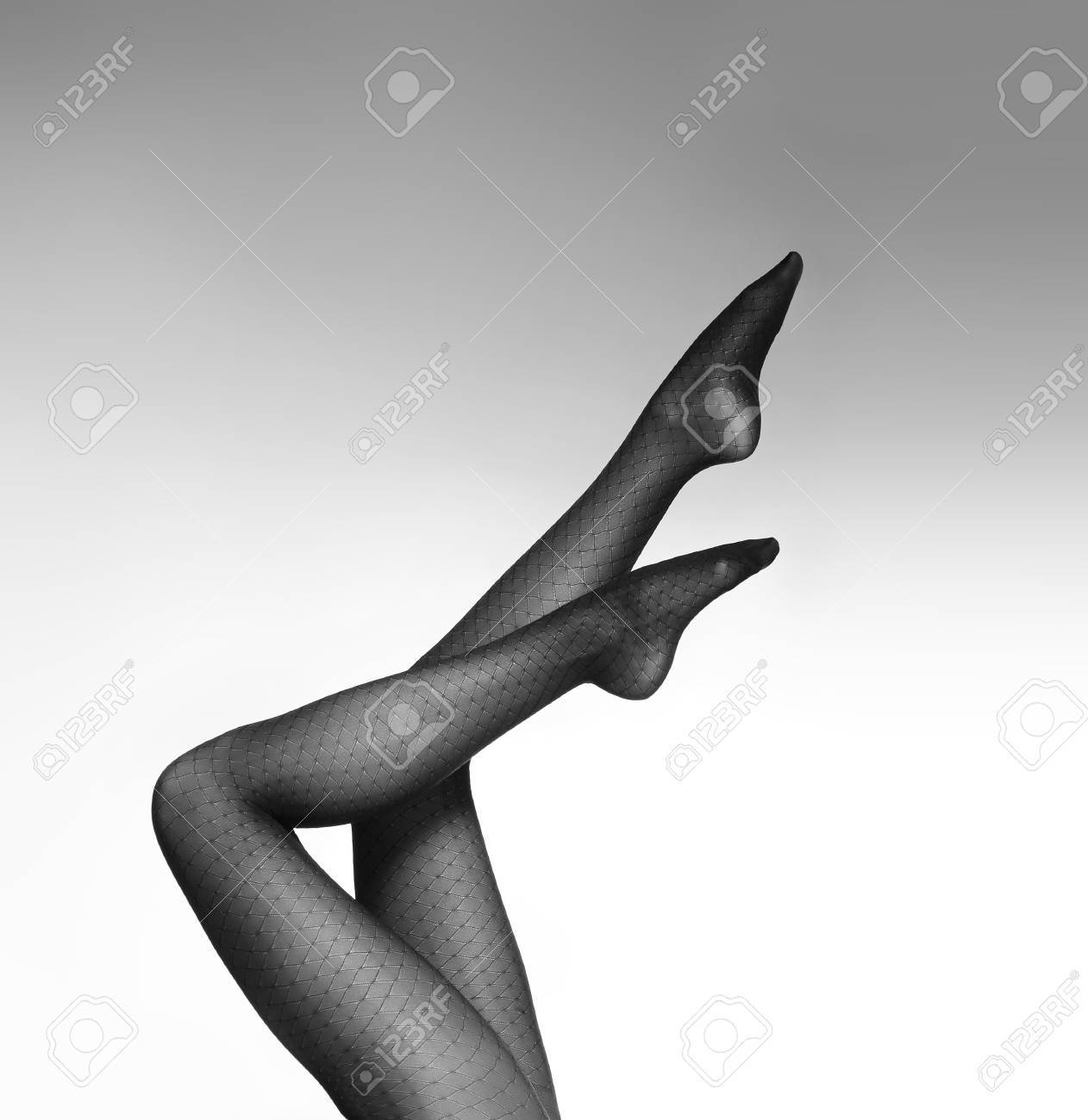 Black and white photo of the beautiful legs in nice stockings over white background stock photo