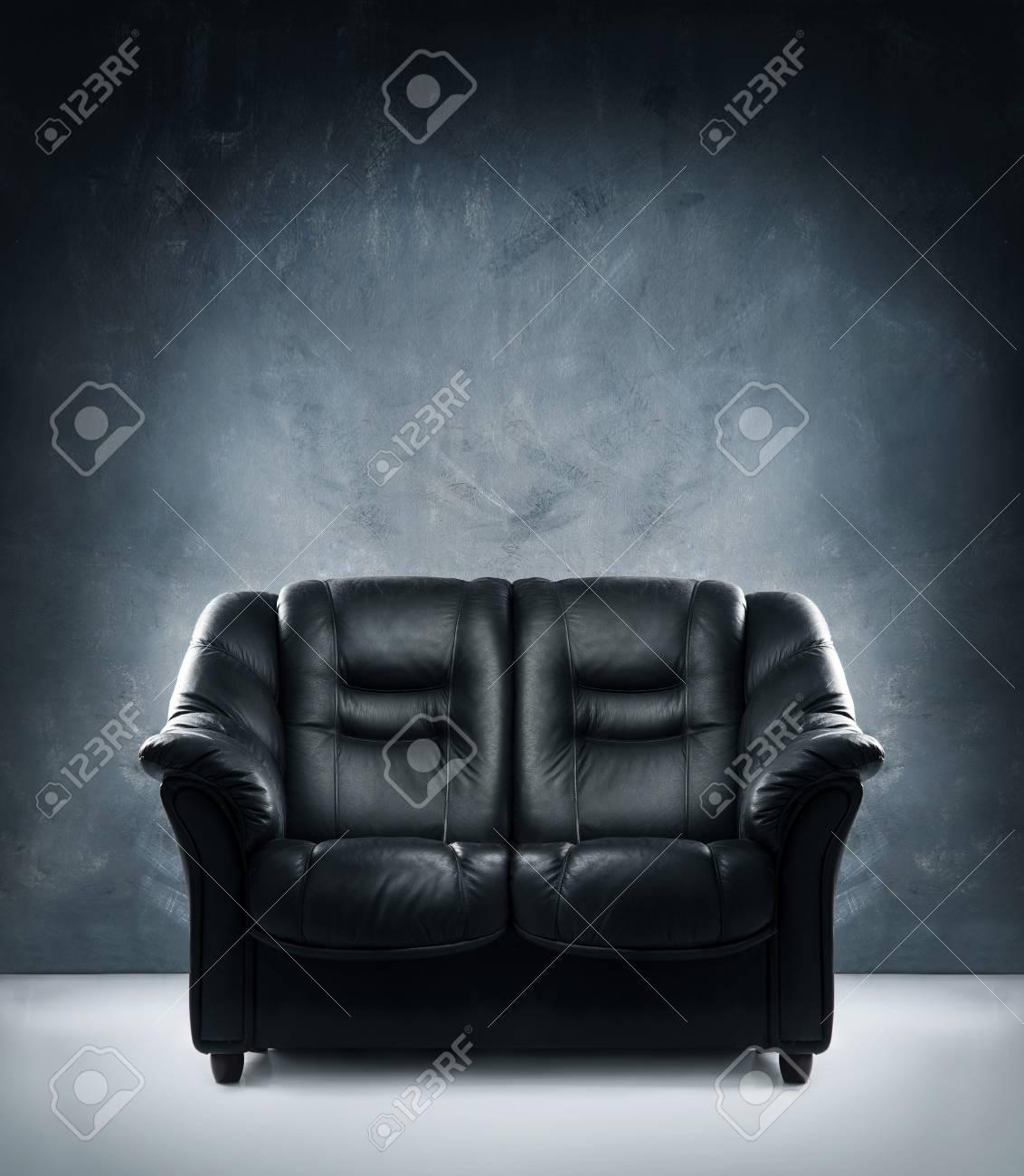 7b0afa2b426 Black leather sofa in dramatic interior Stock Photo - 44633531