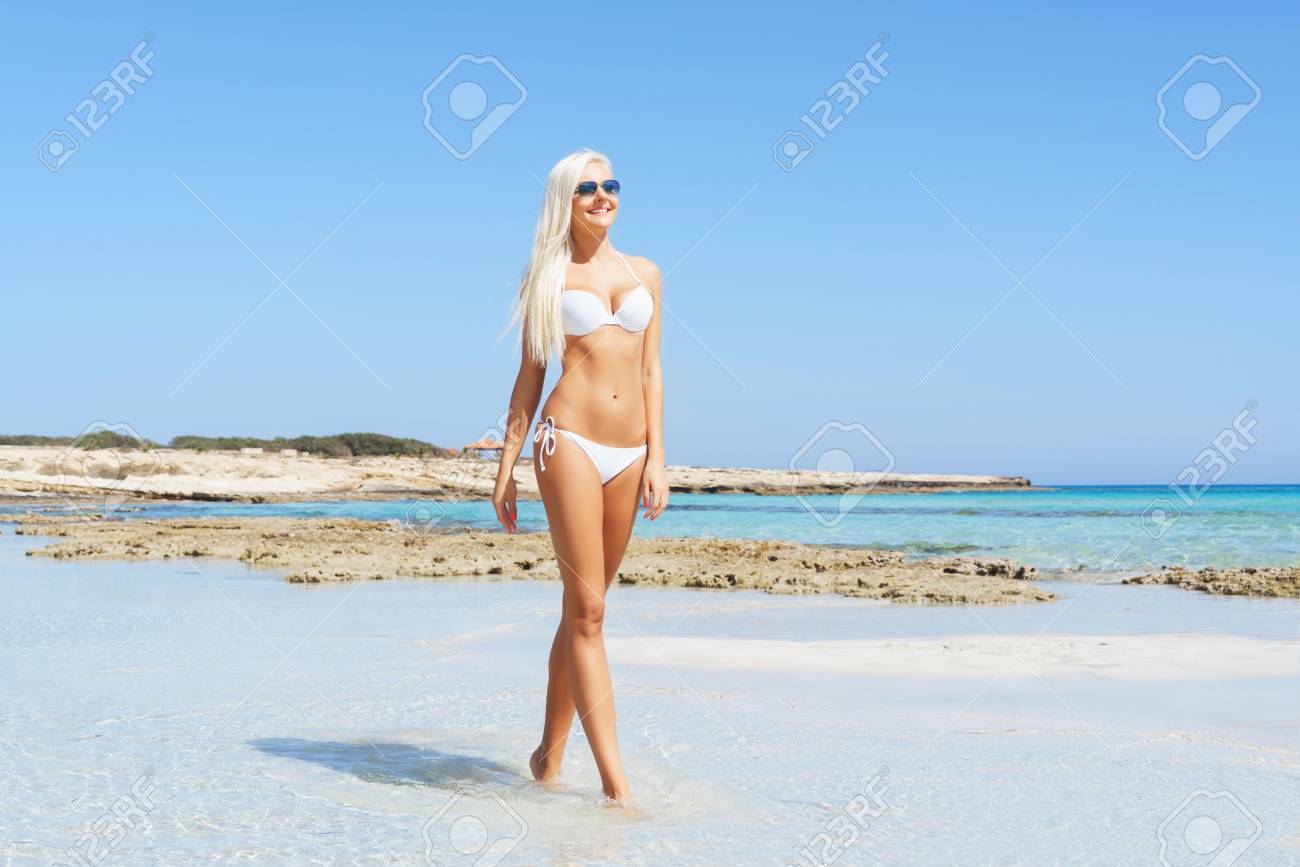 ca8d1ddf18 Beautiful woman in bikini. Young and sporty girl posing on a beach at summer .