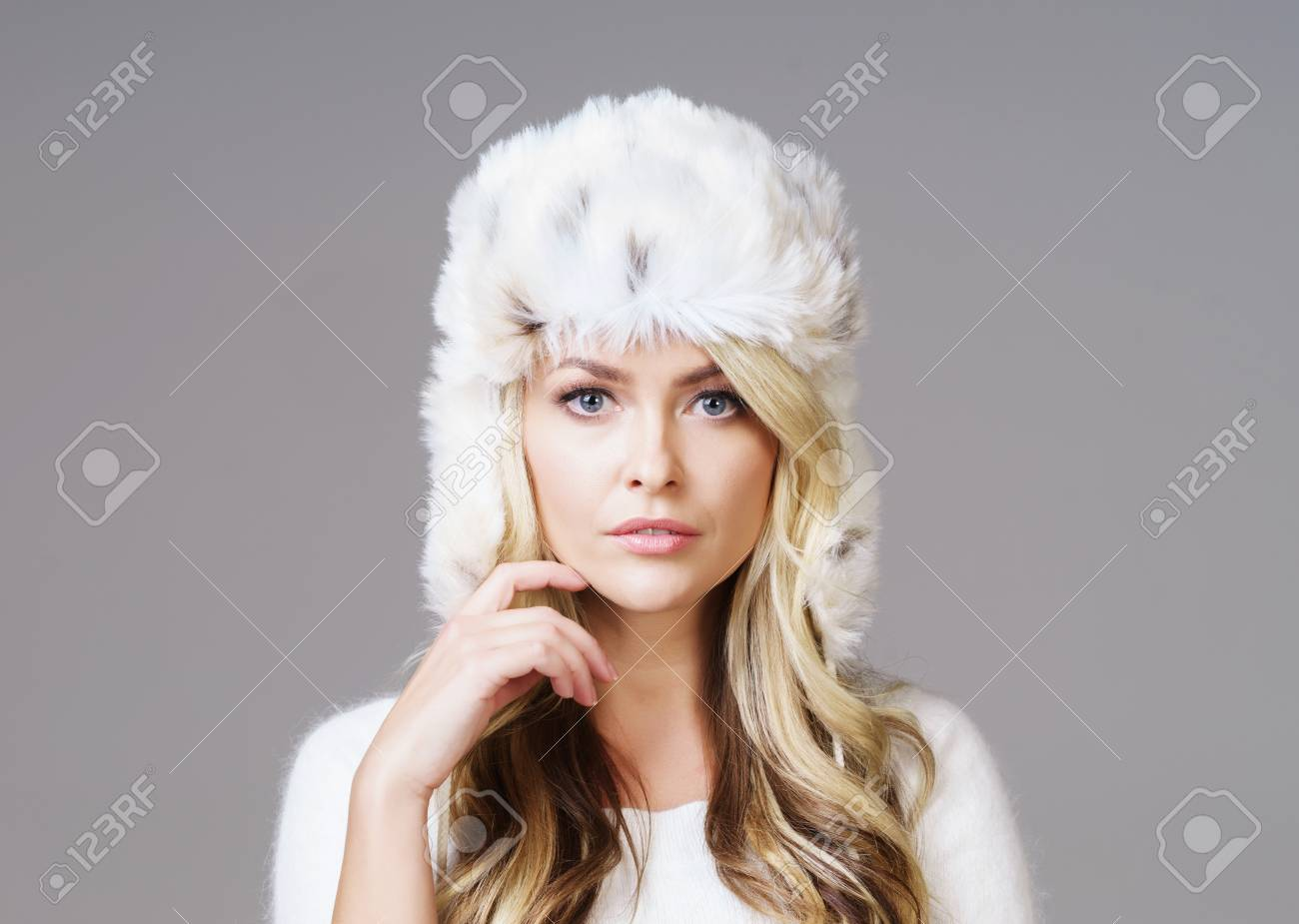 3c32f9a1539f Portrait of young and beautiful woman in winter wear. Grey background.  Christmas, xmas