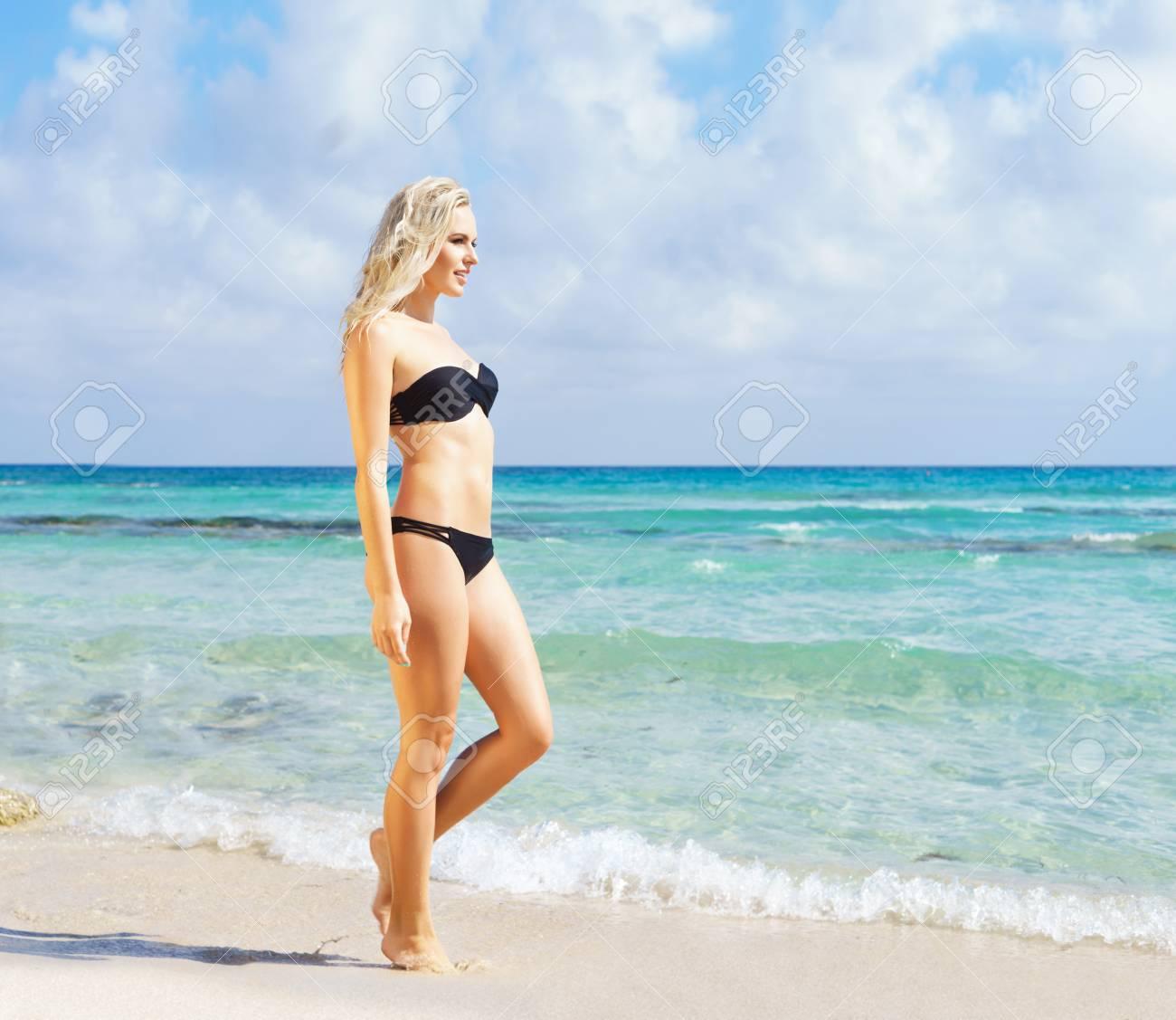 e70fa836b1 Beautiful woman in black bikini. Young and sporty girl posing on a beach at  summer