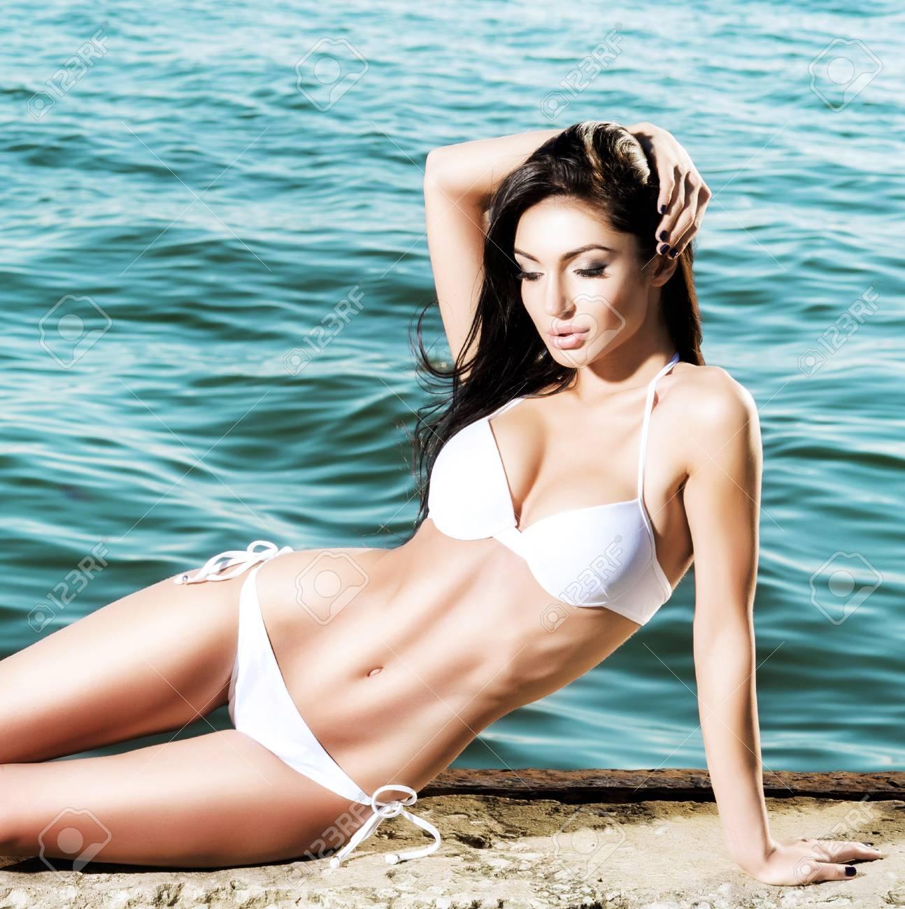f86423f64507 Mujer hermosa, en forma y sexy en traje de baño. Modelo de moda posando en  traje de baño blanco en verano.