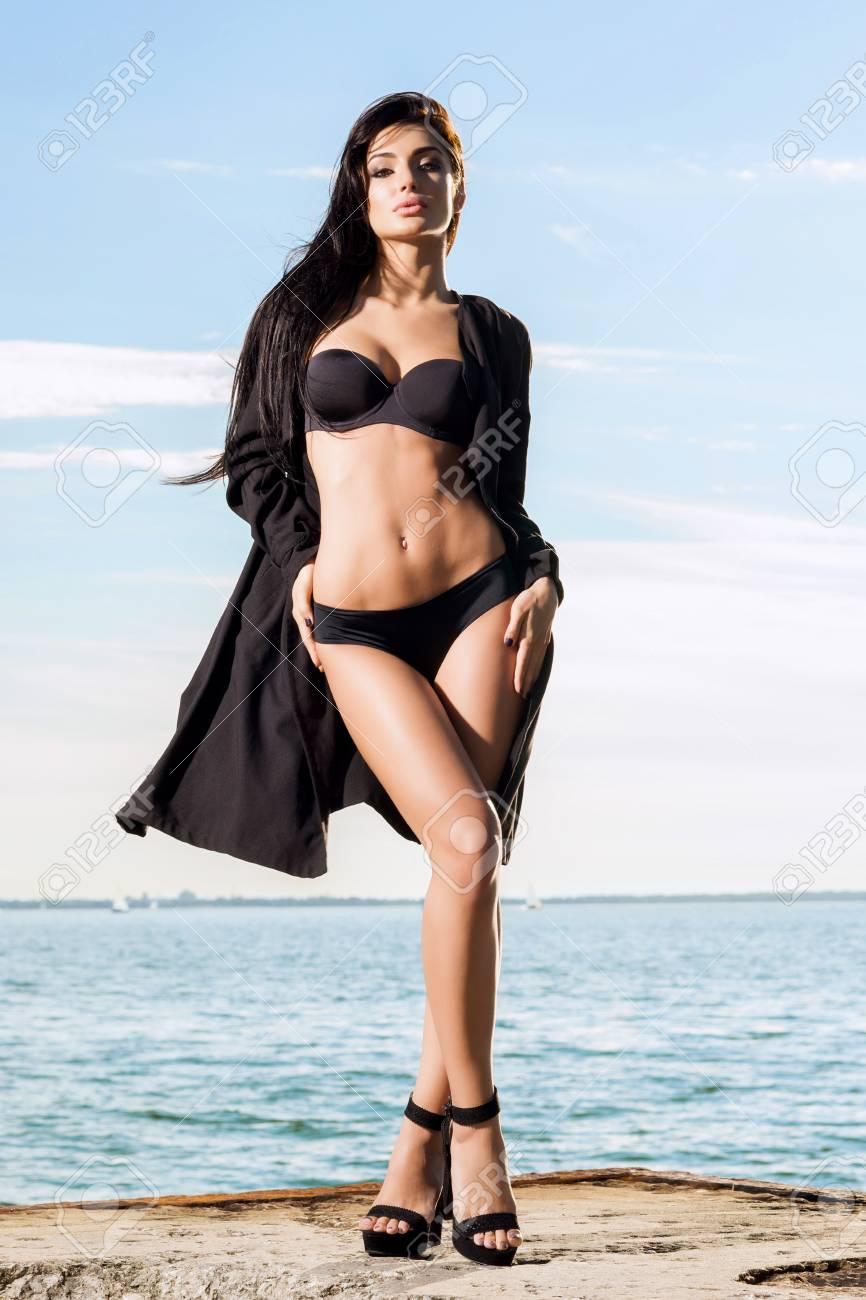 e179e05f400e Modelo de moda hermoso y en forma en traje de baño. Mujer posando en un  muelle en verano sobre fondo de cielo.