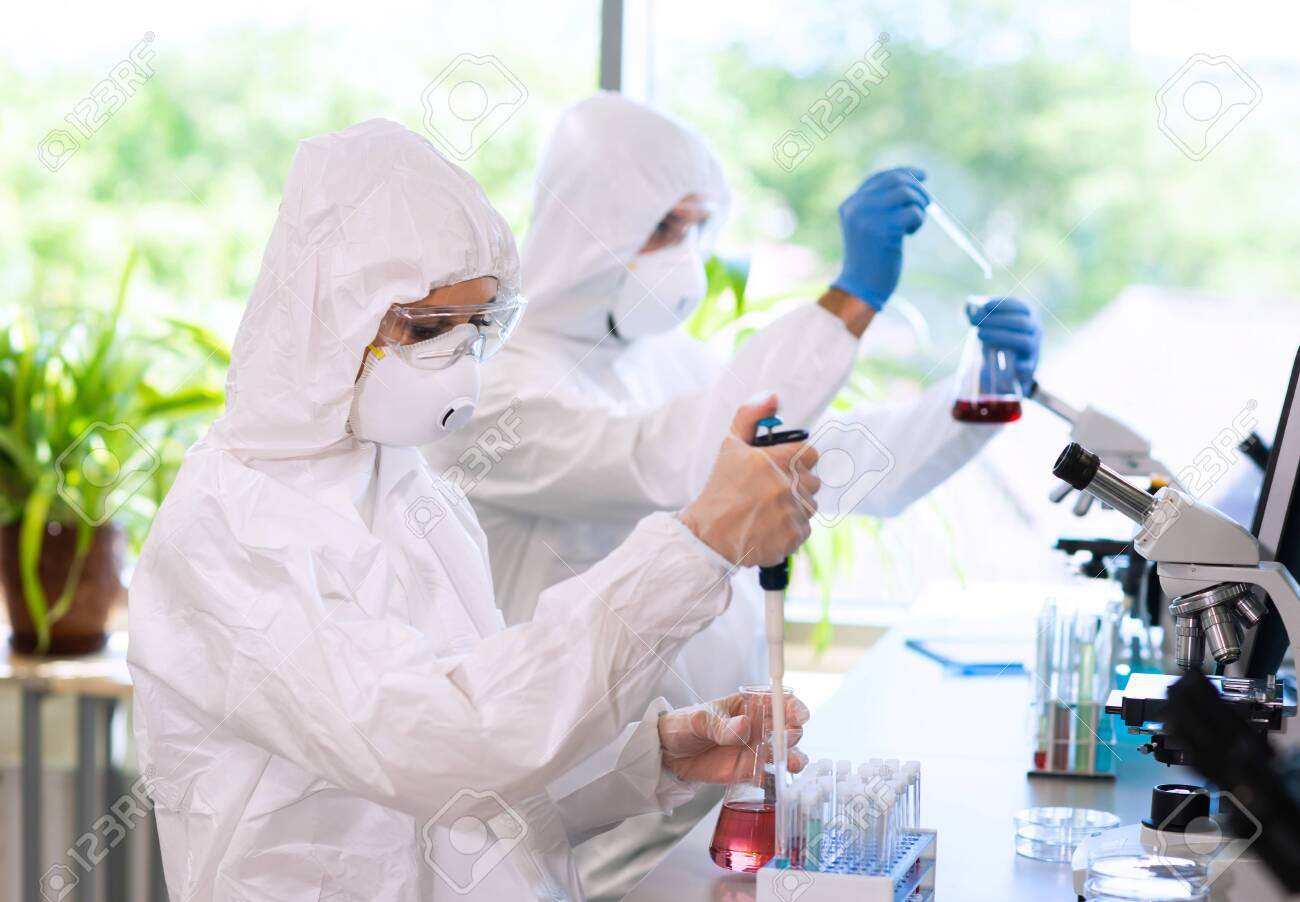 Scientists in protection suits and masks working in research lab using laboratory equipment: microscopes, test tubes. - 127901364