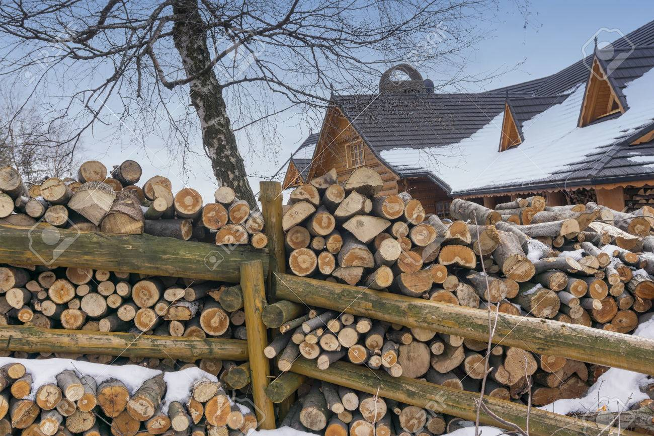 Rustic Wood Fence Background firewood stacked next to the wooden fence, winter, snow. rustic