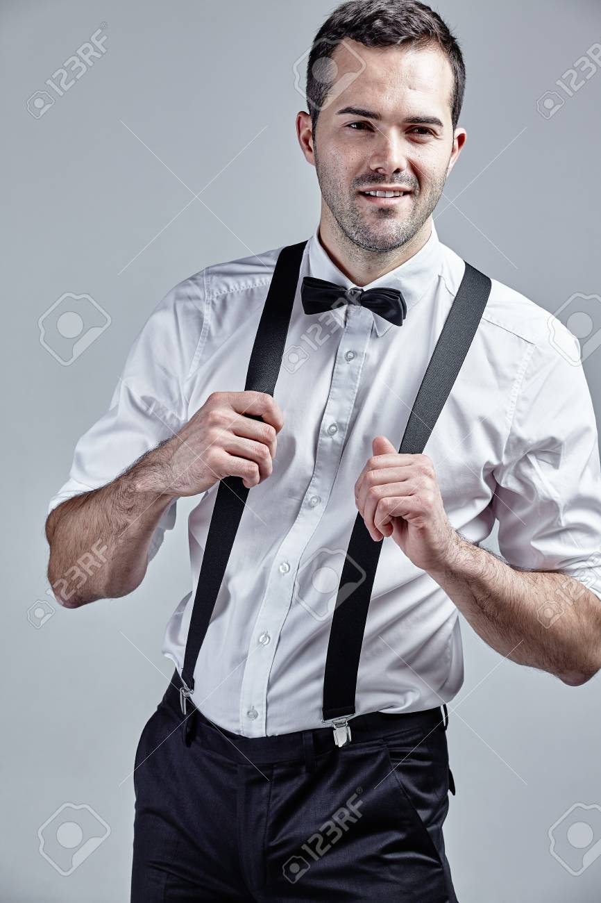4e8145ddff5565 Fashionable man with suspenders and bow tie isolated over grey Stock Photo  - 50087739