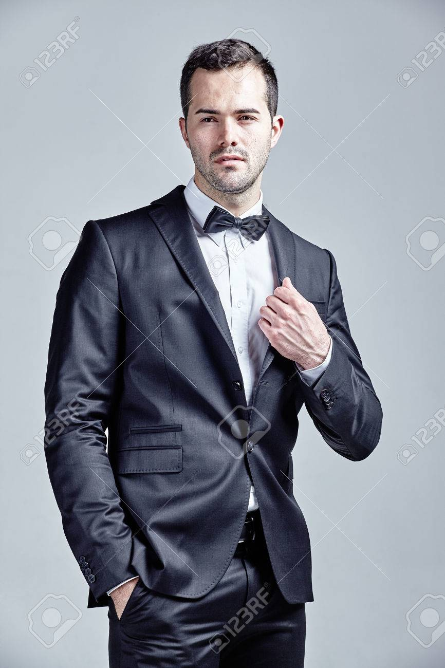 Young Man Wearing Bow Tie And Black Suit Isolated Over Gray Stock ...