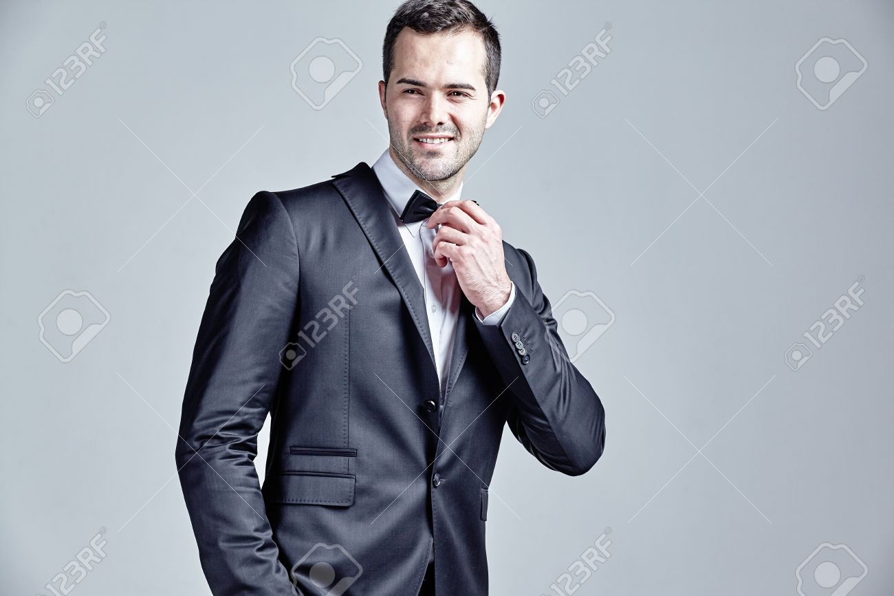 Man Adjusting His Bow Tie Wearing Black Suit Isolated Over Grey ...