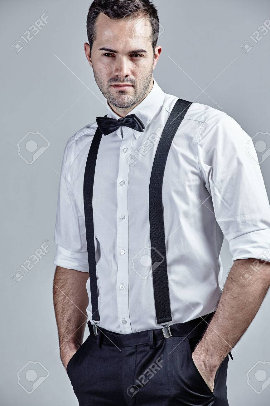 a8799864ef540a Man with suspenders and bow tie isolated over grey Stock Photo - 50088742
