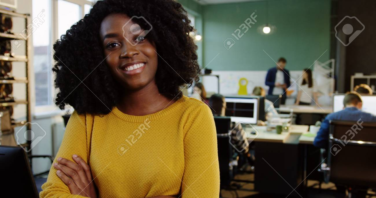Portrait shot of young attractive curly African American woman smiling into the camera in the modern office. Working people on the blurred background. Close up. - 92759587