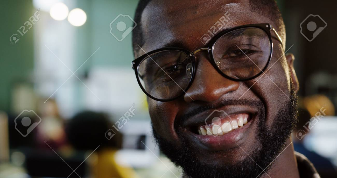 Close up of young attractive African American male office worker in glasses turning his head to the camera and smiling in the urban office. Working people on the blurred background. Portrait - 92982663