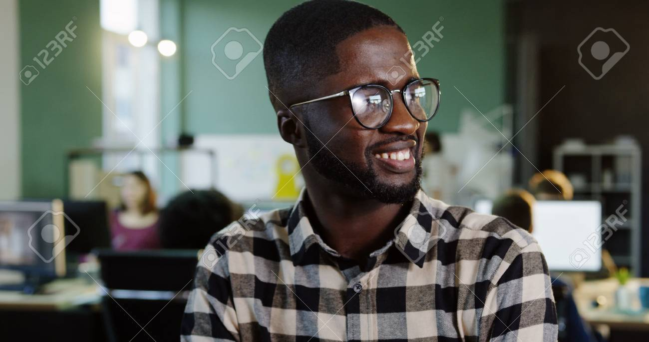 Portrait shot of young African American man in glasses turning his head to the camera and smiling in the modern office. Working people on the blurred background. Close up - 92790410