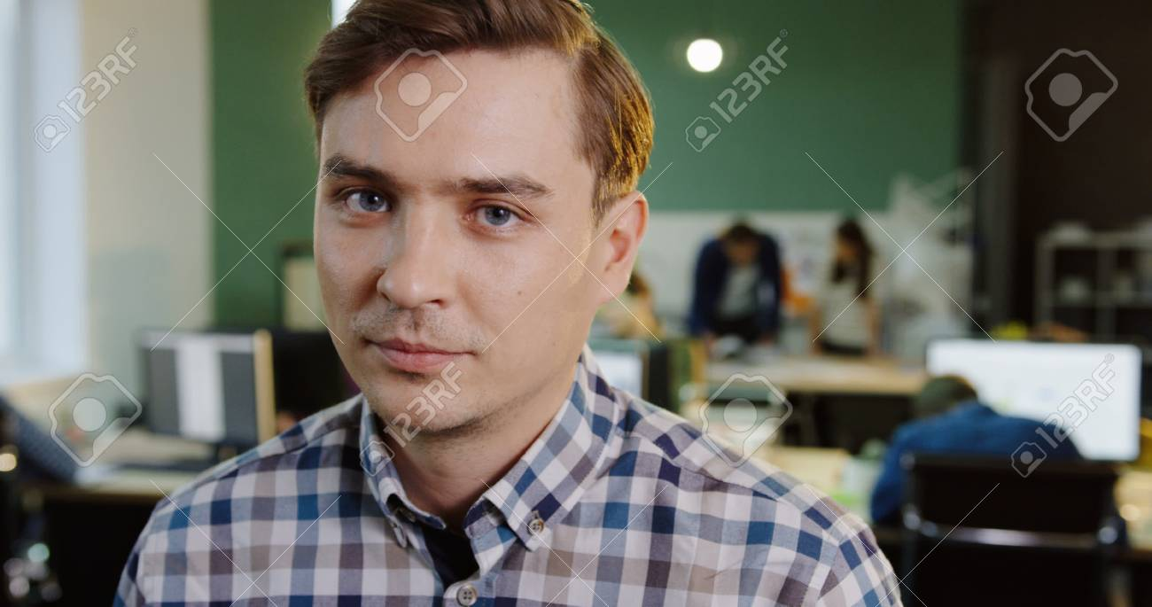 Close up of young caucasian male office worker turning his head and smiling into the camera in the modern office. Working people on the blurred background. Portrait - 92950679