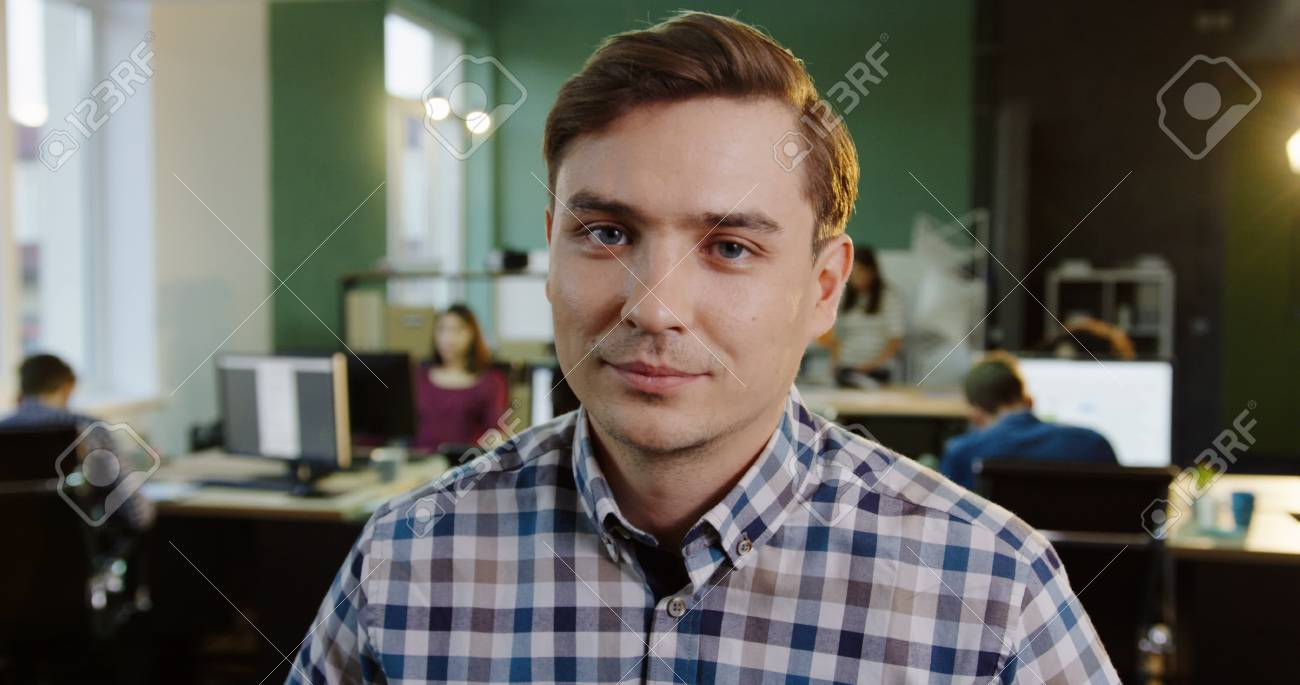 Close up of young handsome caucasian man turning his head and looking into the camera in the urban office. Working people on the blurred background. Portrait shot - 92909048