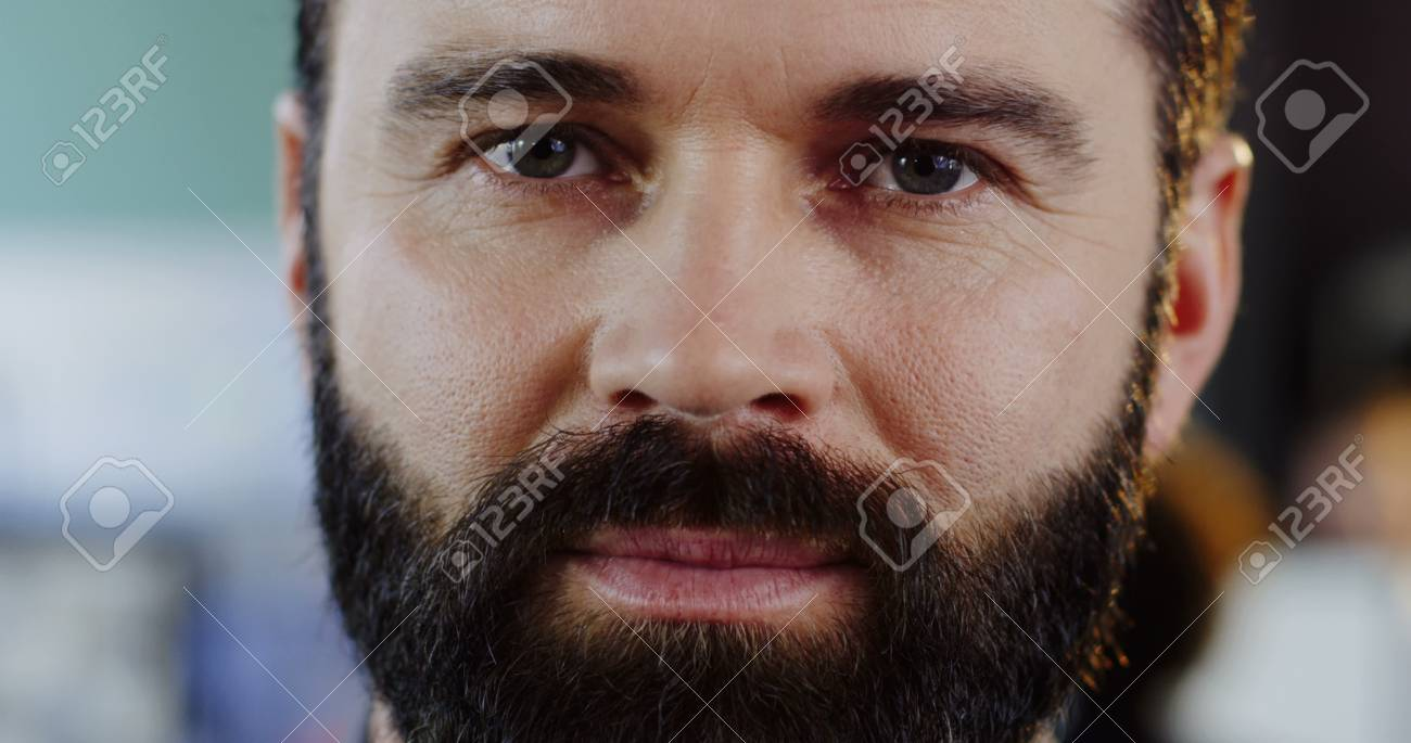 Close up of caucasias man with a beard looking and smiling sincerely straight into the camera. The blurred office with people at computers background. Inside. Portrait - 92663318