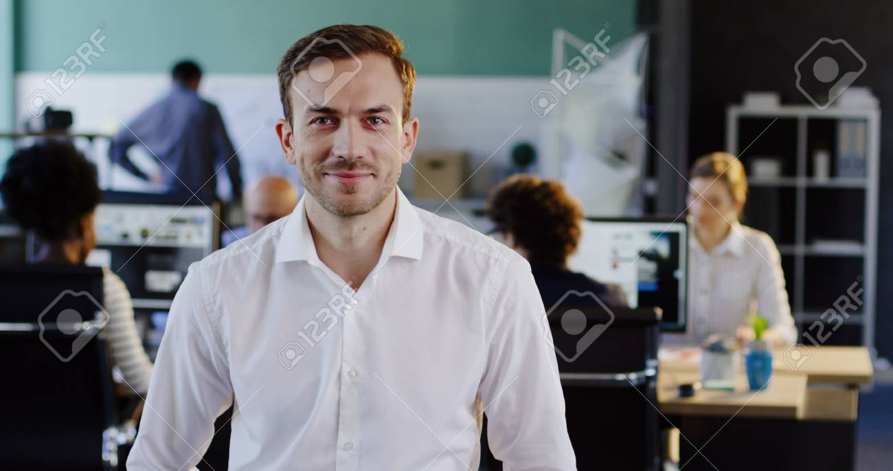 Portrait of attractive young man in white shirt looking into the camera and the blurred office with workers at computers behind. Indoor - 92663641
