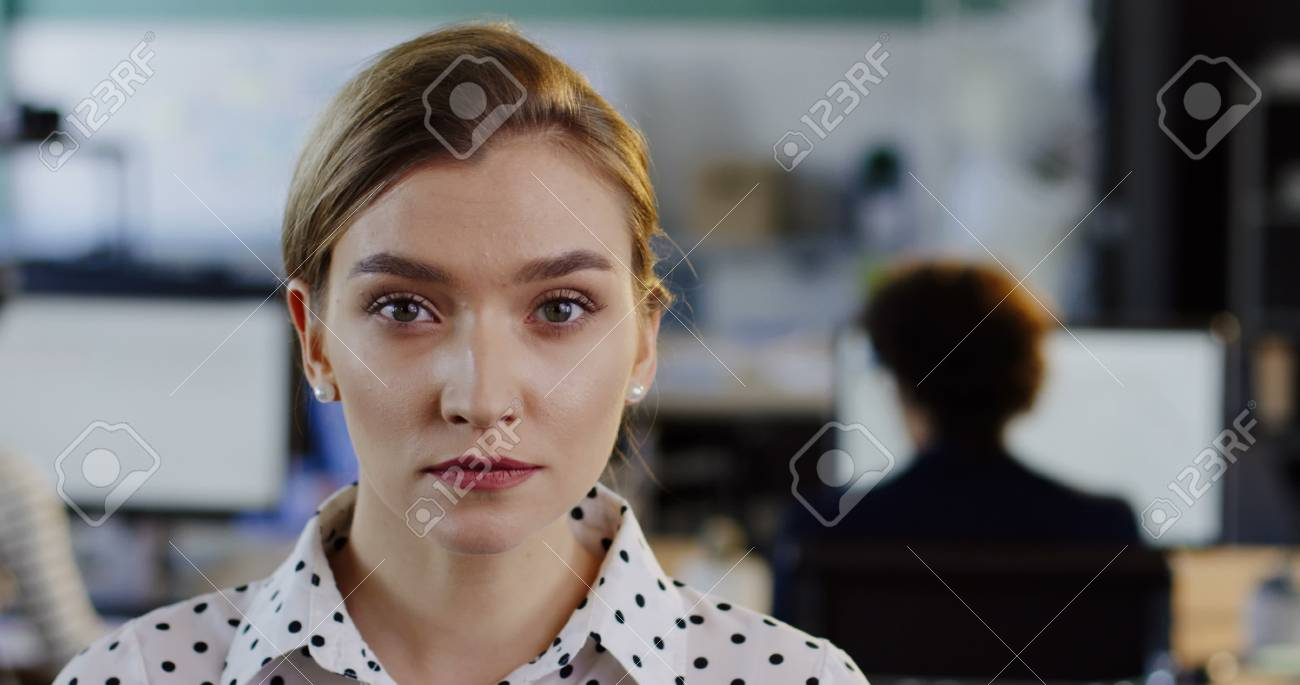 Close up of charming young woman turning her head to the camera and smiling sincerely. The blurred office with workers at computers background. Indoors. Portrait - 92663644