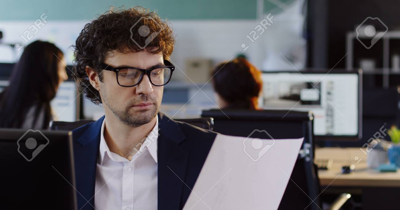 Male office worker sitting at the computer and working with printed documents in the modern office room. Indoor - 92663650