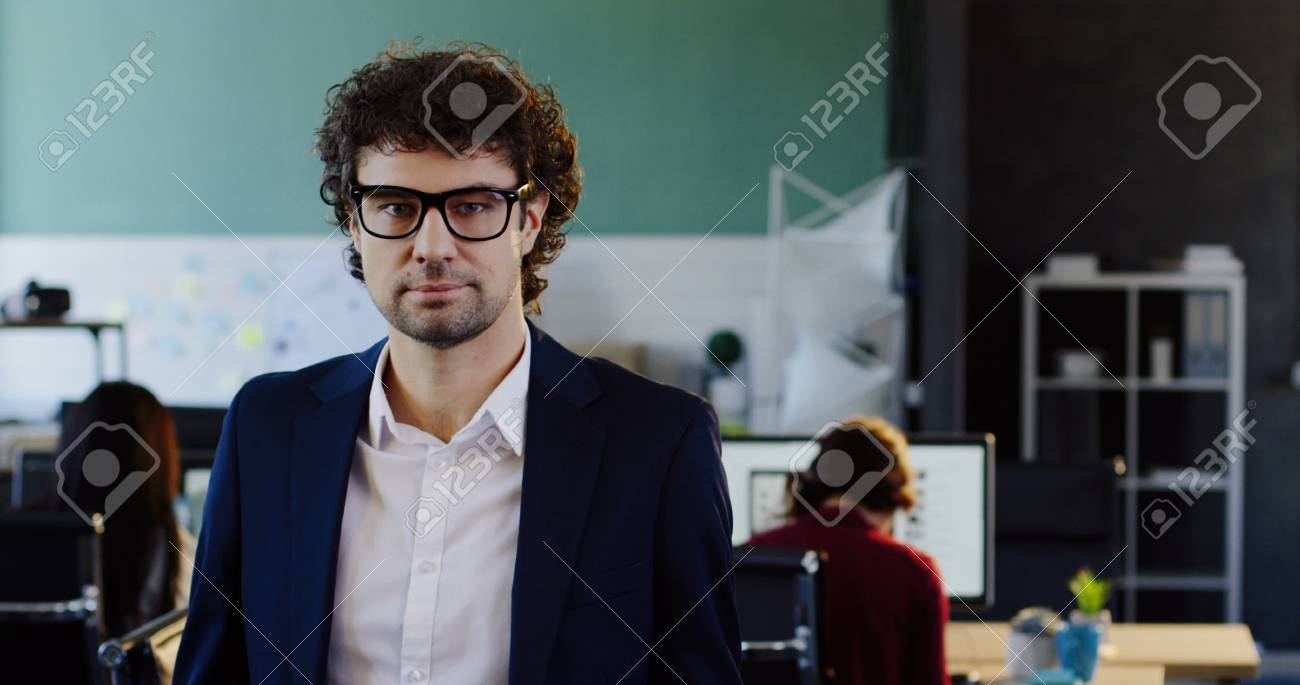 Portrait shot of attractive caucasian young man looking into the camera and taking off his glasses. The blurred office with workers at computers behind. Indoors - 92663652