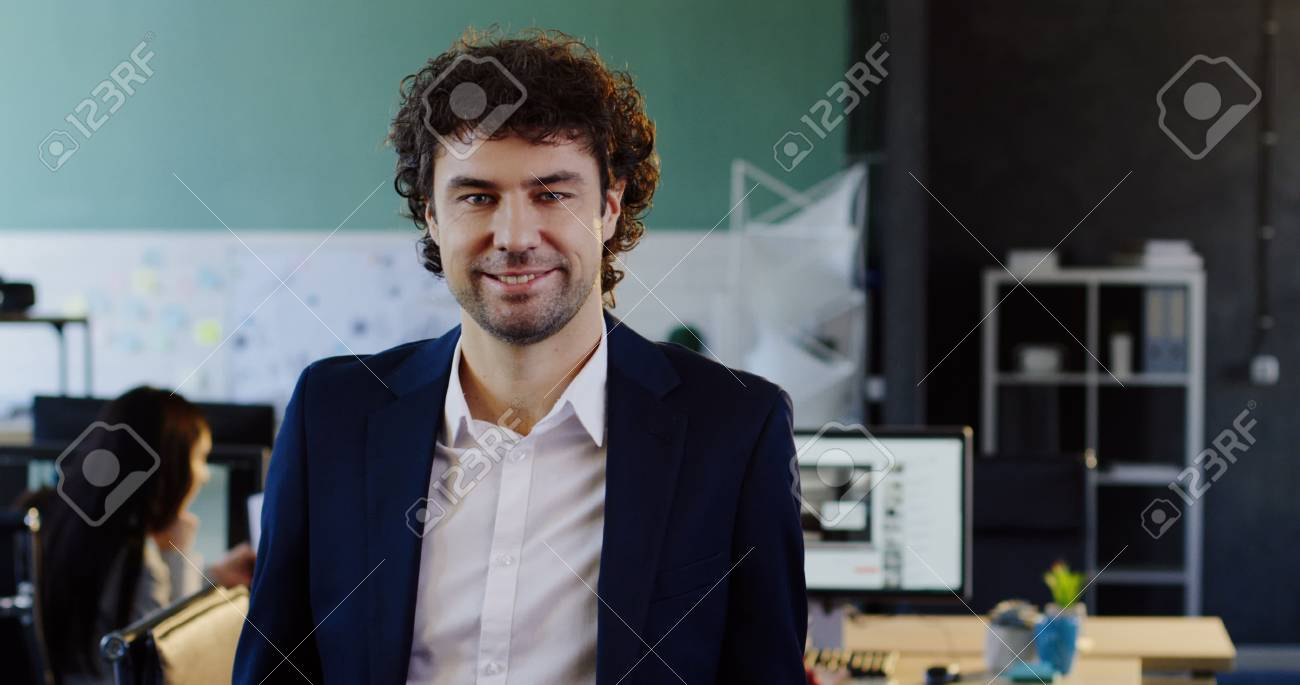 Portrait shot of attractive caucasian young man looking into the camera and taking off his glasses. The blurred office with workers at computers behind. Indoors - 92663653