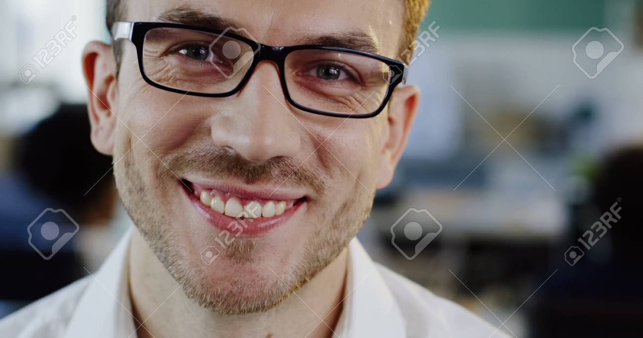 Close up of Caucasian attractive young man in glasses looking and starting to smile sincerely into the camera. The blurred office space background. Portrait shot. Indoor - 92663656