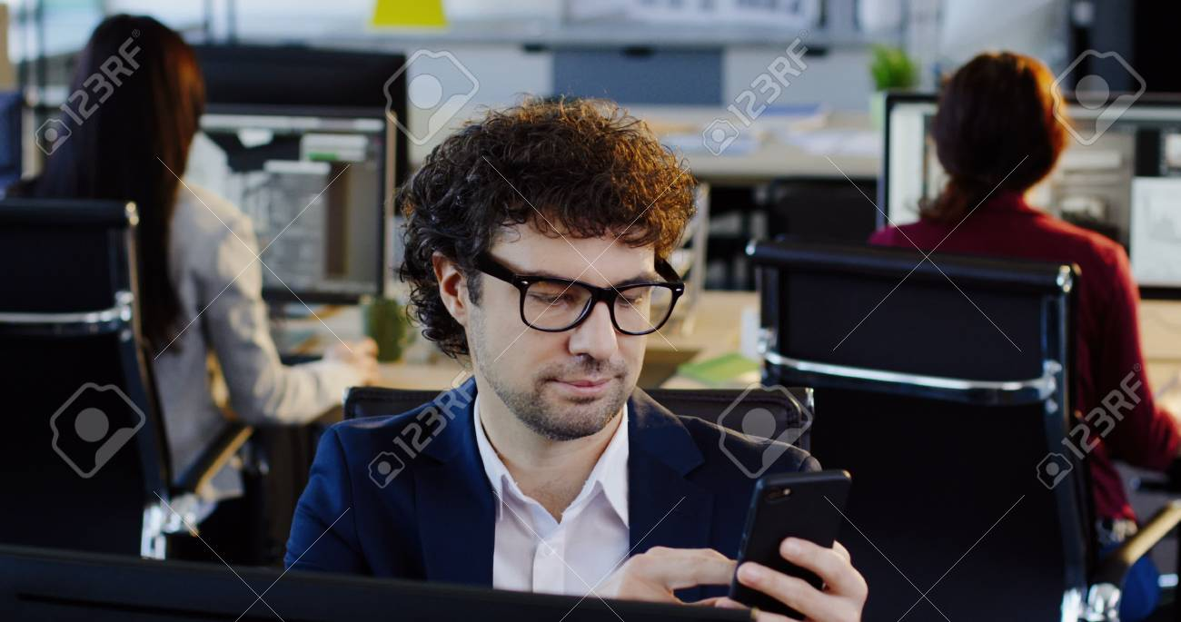 Portrait shot of curly attractive man in glasses scrolling on the mobile phone while sitting on his workplace in the office. The background of working office employees. Indoors - 92663725