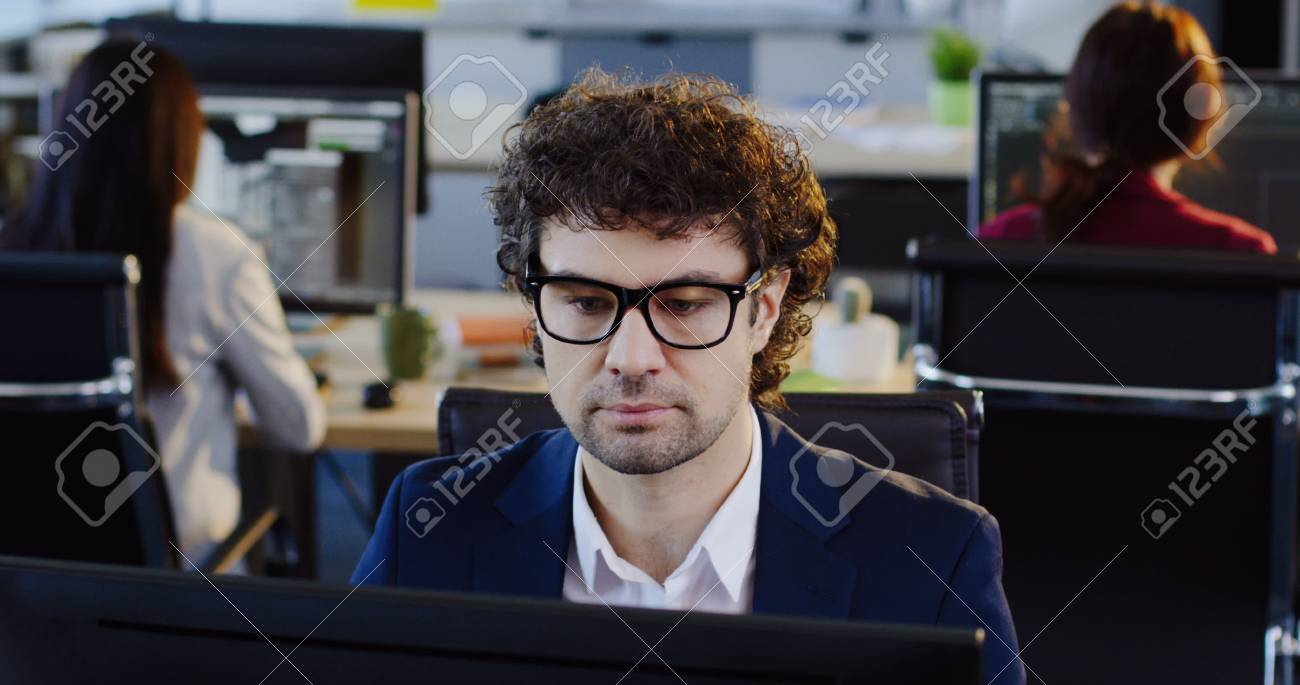 Close up of appeling male office worker in glasses sitting on his workplace in the big company office and working at the computer. The background ooffice workers at their tables. Inside - 92663727