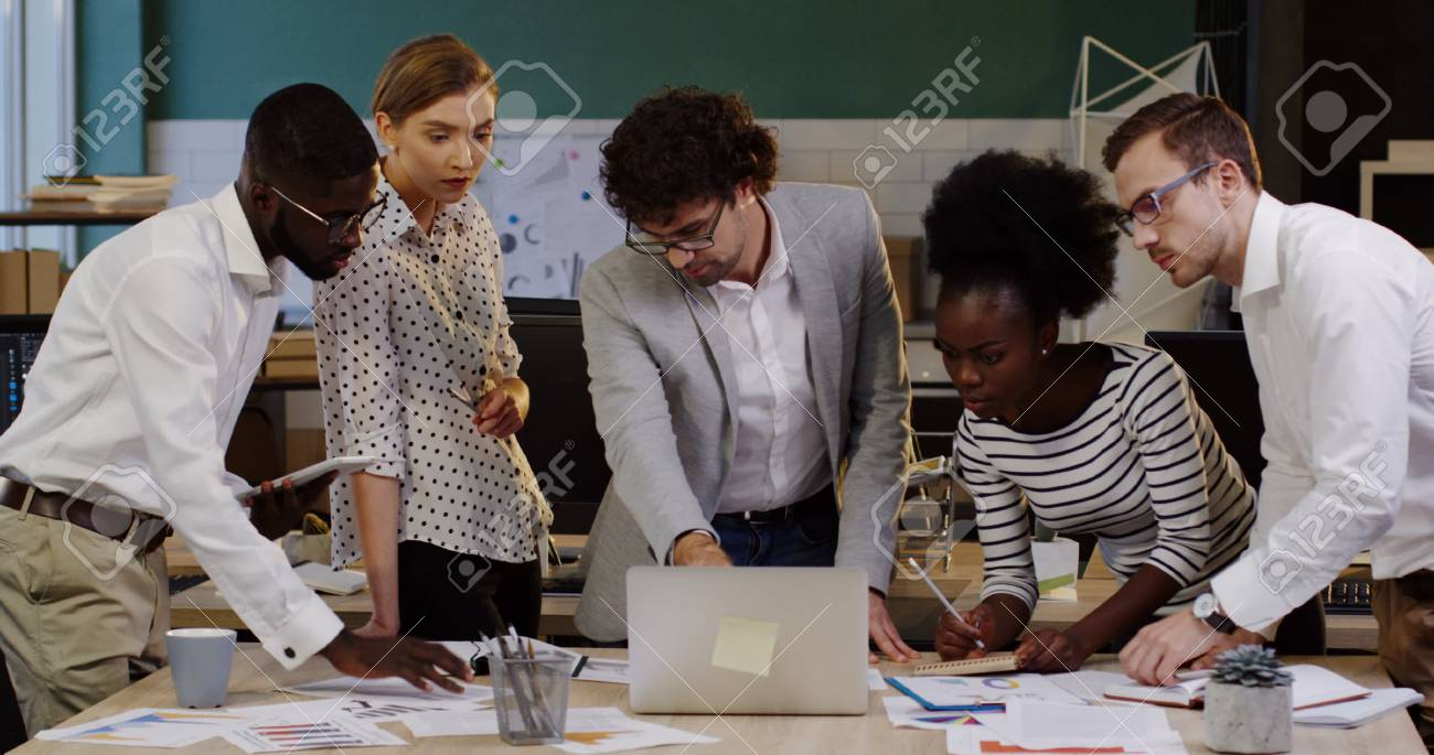 Young business team of multi ethnical office workers checking the data and working on a new startup project while standing around the table with documents, charts, graphics and financial reports on it. - 92663751