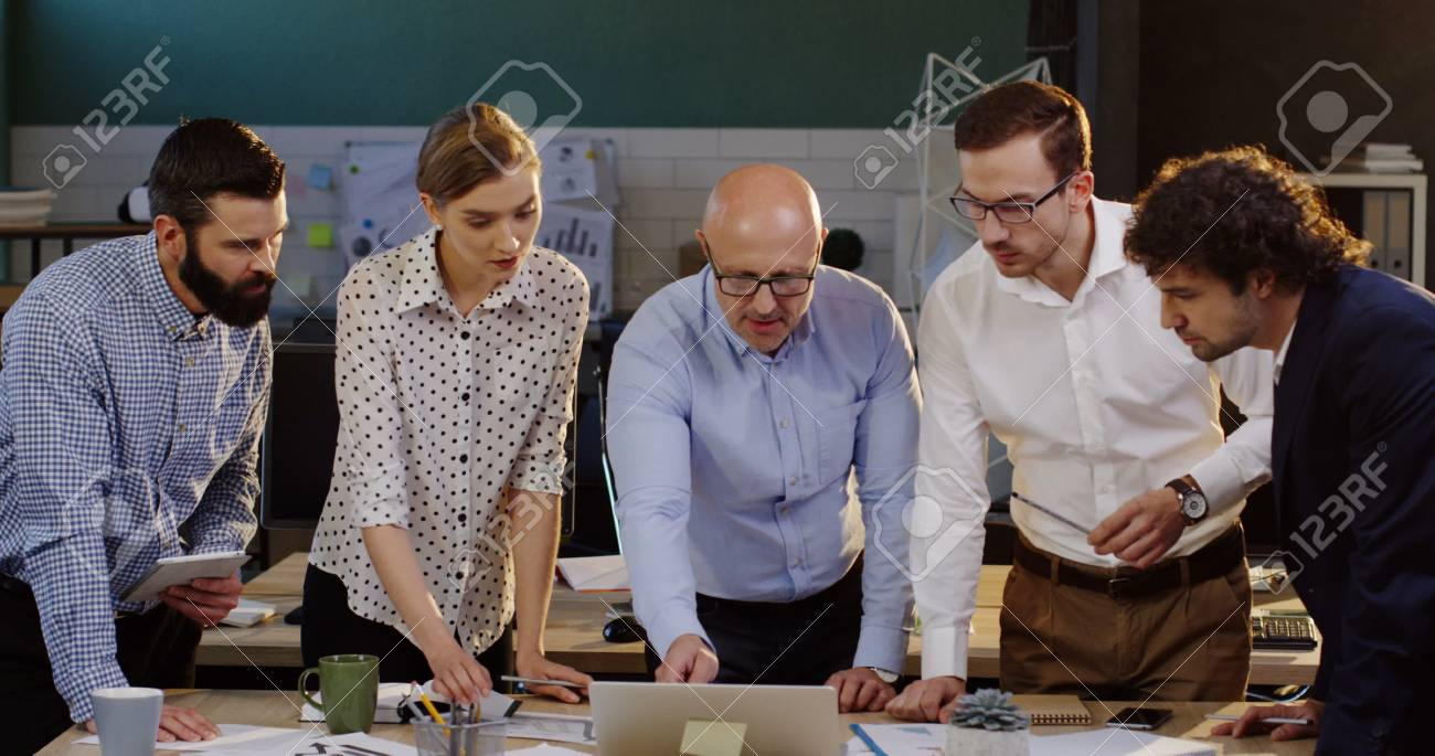 Young team of business employees standing around a table with documents, charts, graphics and financial reports and discussing cheerfully their project with a boss. - 92663791