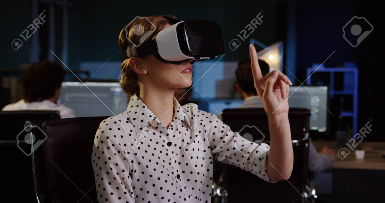 Young female office worker having a VR headset at her workplace in the evening. VR glasses. - 92663939