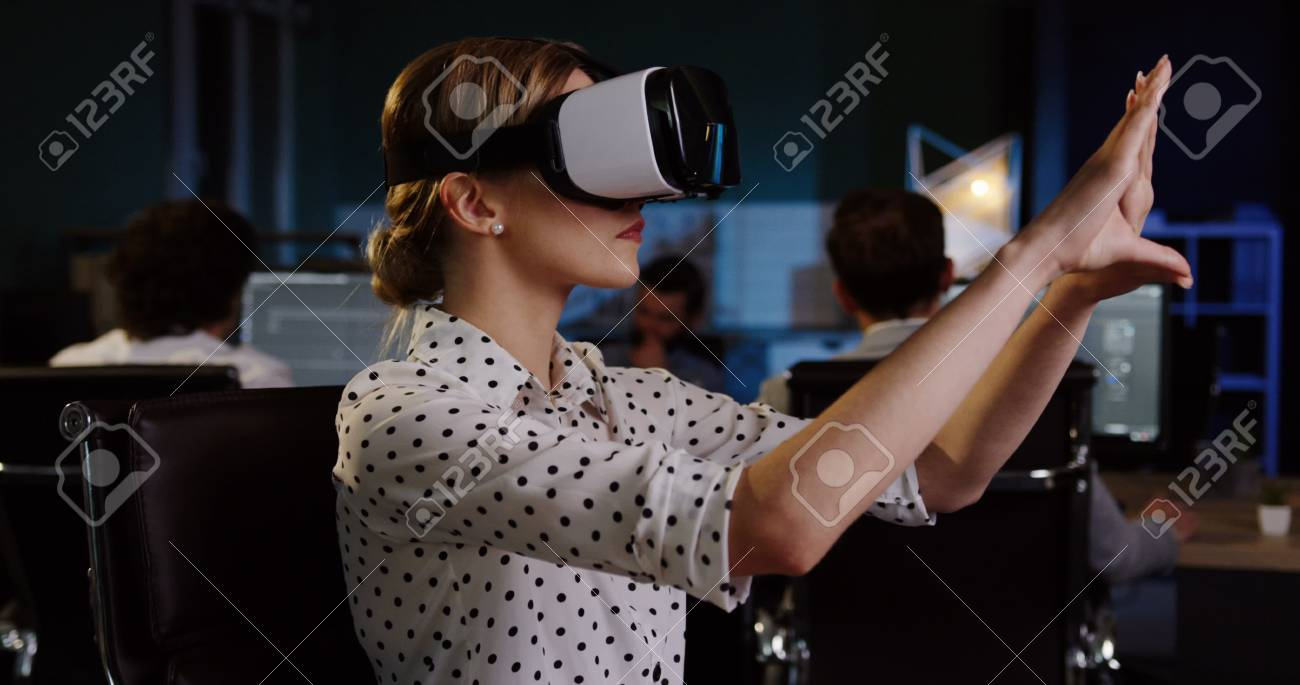 Young female office worker having a VR headset at her workplace in the evening. VR glasses. - 92663940