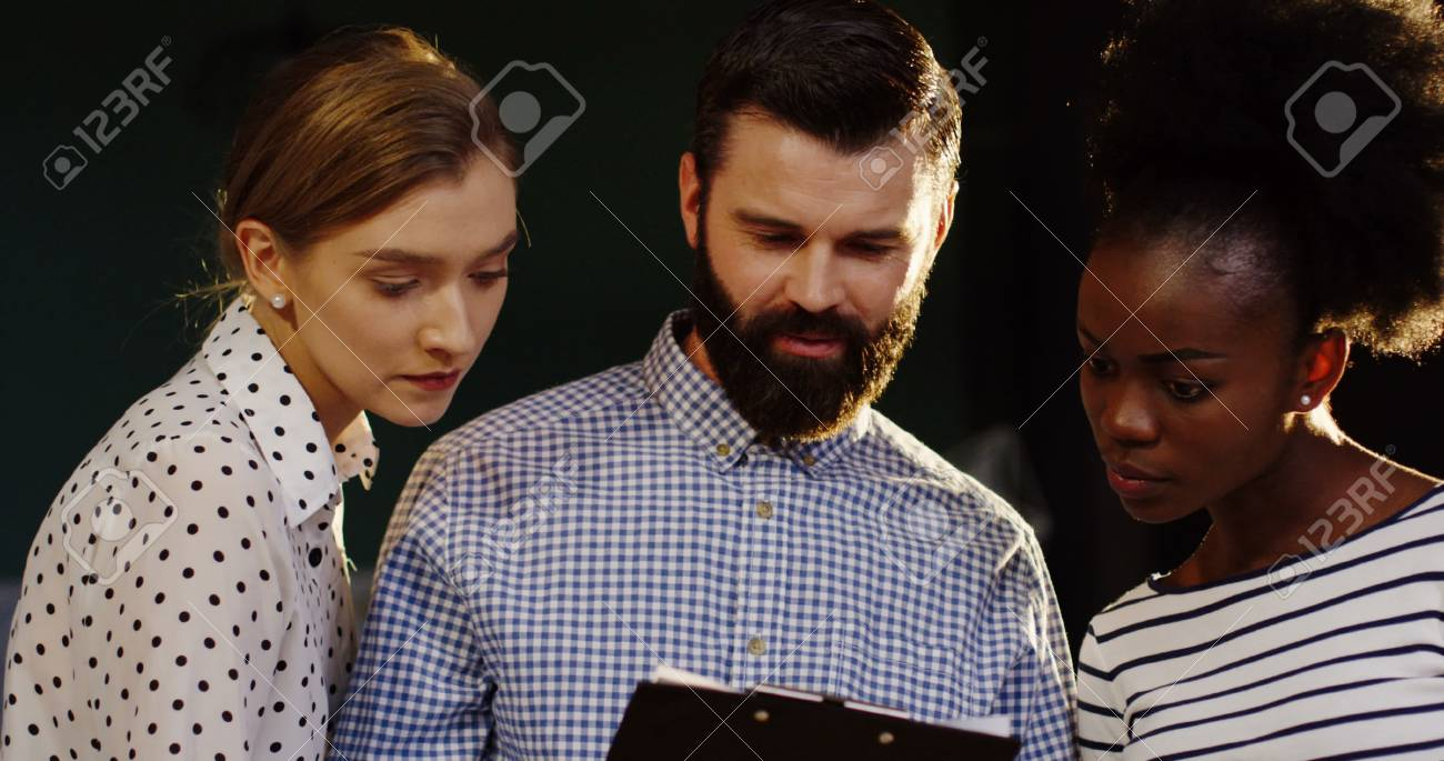 Close up of a caucasian man standing with two co-workers mixed races women and discussing something late in the office. - 92664013
