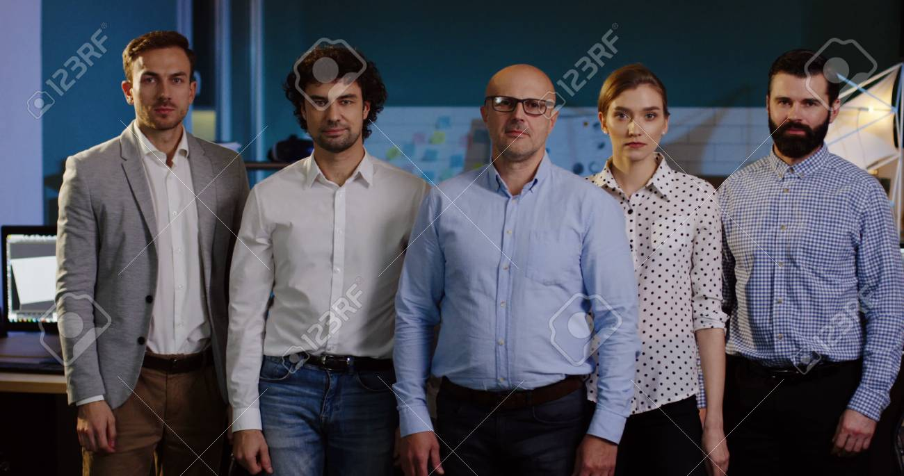 Portrait of office workers team with their boss posing in the modern office space and crossing their hands. - 92664015