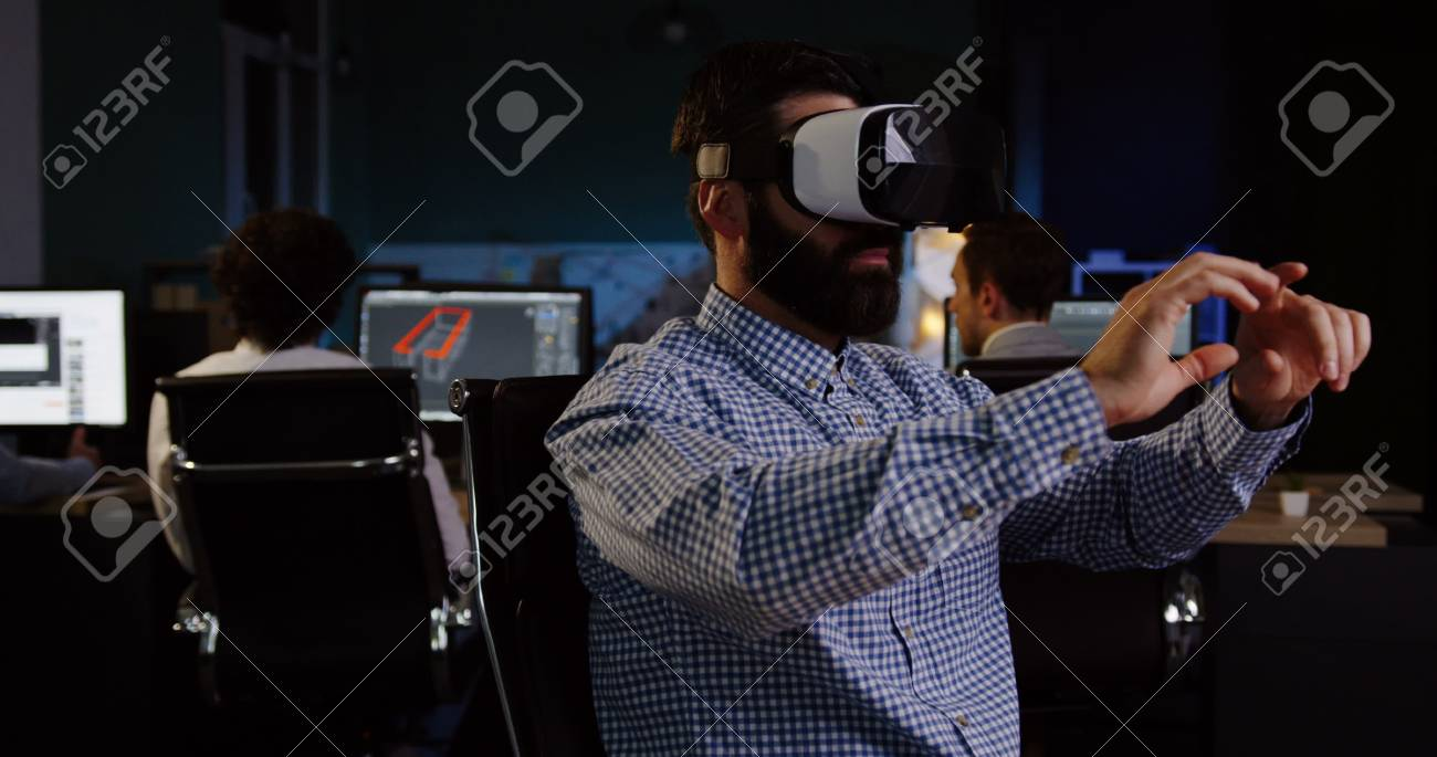 Male office worker with a beard having a VR headset at his workplace in the evening. - 92664053